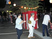 夏祭りの画像です。提灯や紅白のたれまくの下でみなさん踊っています。