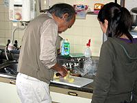 居宅生活訓練の画像です。男性がスタッフの指導の元、調理の実習をされています。
