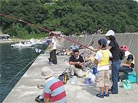 一泊旅行の画像です。岸壁で魚釣りを楽しんでいます。
