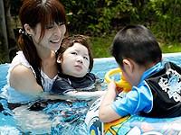 夏の屋外プールの画像2枚目です。子どもさんが介助されながら水を楽しんでいます