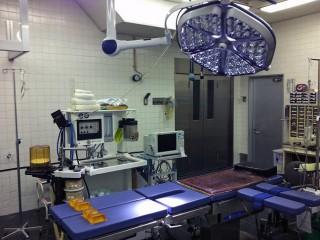 手術室の画像です。中央に手術専用のベッド台と大きな照明器具があります。奥に専用の医療機械が配置されています。