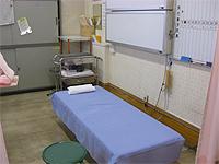 診察室の画像です。青いシーツが敷かれた診察用ベッドが配置されています。