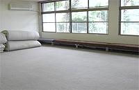 多目的ホールの画像です。白い壁に床は灰色のカーペットです。広くて色々な活動に使うことができます。