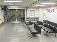 待合室の画像です。広めの部屋に黒い長椅子が6脚並べられています。