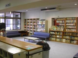 談話室、図書室の画像です。各種書籍が並んでいます。部屋中央と壁際に青い長椅子が配置されています。