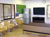 デイルームの画像です。ベージュの椅子と長椅子があります。壁には冷蔵庫とテレビが配置されています。