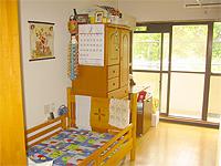 居室2人部屋の画像です。木調のベッドと引出し、大きい窓が特徴です。外の光が豊富に入り明るい部屋です。