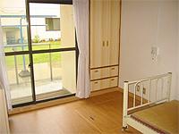 居室の画像です。木調の床、白い壁、大きな窓があります。明るい部屋です。