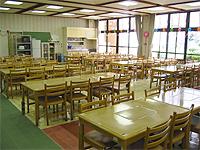 食堂の画像です。木製の机と椅子が並べられています。かなり広めの部屋です。