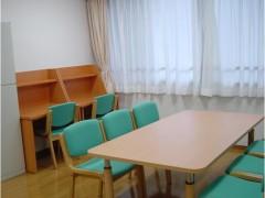 学習室の画像です。壁際に机と椅子が2セット、中央机があり、6脚の椅子が並べられています。