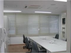 事務所の画像です。白いオフィスデスクと黒い机が配置されています。