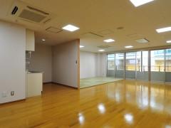 集会室の画像です。フローリング床に一部畳のエリアがあります。壁が一面窓のため、豊富に外の光が入ります。