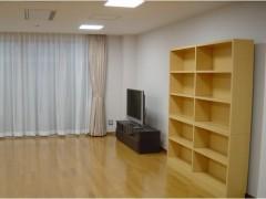 集会室の画像2枚目です。テレビと木製の棚が配置されています。