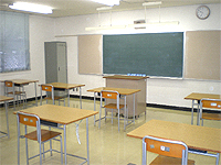 教室の画像です。前方に黒板、教壇、部屋には椅子と机が配置されています。