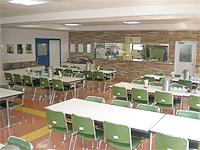 食堂の画像です。バイキングレストランのような高級感があります。白い机と緑の椅子があり、かなり広く作られています。