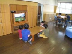 プレイルームの画像です。フローリングの床の上で子どもたちがテレビを見ています。