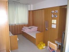居室の画像です。木製のきれいなベッドが2つ並んで配置されています。