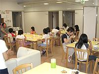 リビングの画像です。スタッフと子どもさんが食事をしています。机と椅子の他に大きなソファもあります。