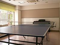遊戯室の画像です。中央に卓球台があります。窓が大きいため、外の光が豊富に入りとても明るい部屋です。