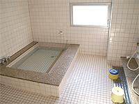 浴室の画像です。全体がタイル張りです。広めの湯船と一般的なシャワーブースがあります。