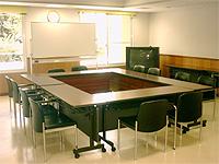 会議室の画像です。机が四角形に並べられて4辺に黒い椅子が配置されています。