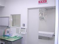 レントゲン室の画像です。白い部屋の中央に撮影器具とベッドが配置されています。