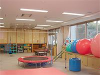 理学療法室の画像です。トランポリンや大きなボールがおいてあります。比較的広い施設です